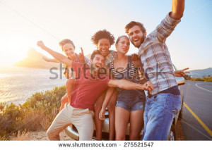 stock-photo-group-of-friends-standing-by-car-on-coastal-road-at-sunset-275521547